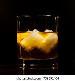 Amber color hard liquor on rocks on black