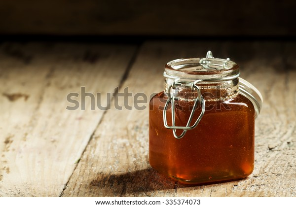 Amber dark honey in a glass jar on the old wooden table, selective focus