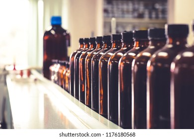 Amber glass bottle filling with chemical reagent for testing in laboratory room arranged in the quality control division at the pharmaceutical plant (site) or chemical lab in the university or school
