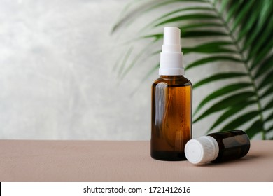 Amber glass bottles with tropical leaf on grey background. Natural organic cosmetic packaging, luxury beauty products for body care