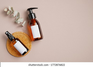 Amber glass cosmetic bottles mockups with blank labels and eucalyptus leaf on beige background. Natural organic beauty product packaging design. Flat lay, top view.