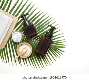 Amber glass cosmetic bottles with spa element and towel with green leaf on marble background. Blank label for branding mock-up. Natural concept.Flat lay, top view.