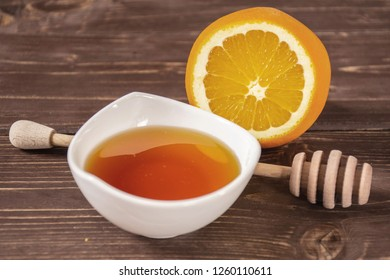Amber honey, deeper and a sliced orange. recipe step by step hot red mulled wine on brown wood