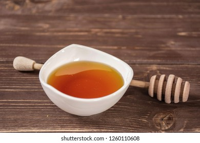 Amber honey in a white bowl with a deeper. recipe step by step hot red mulled wine on brown wood