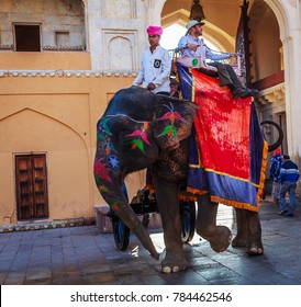 AMBER, INDIA - DECEMBER 25: Unidentified men ride decorated elephants in Jaleb Chowk in Amber Fort on DECEMBER 25, 2017 in Amber, India. Elephant rides are popular tourist attraction in Amber Fort.