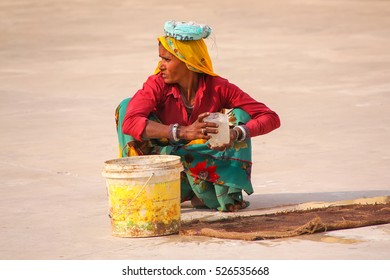 AMBER, INDIA - NOVEMBER 13: Unidentified woman works in the second courtyard of Amber Fort on November 13, 2014 in Amber, India. Amber Fort is the main tourist attraction in the Jaipur area.