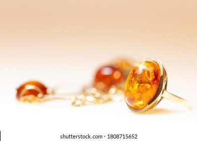 Amber jewelry like necklace, bracelet and ring with noble metal like gold. warm white background with copyspace