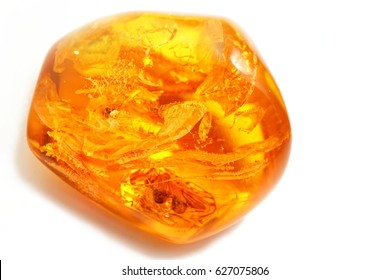 Amber. Largely removed red-yellow polished amber with sparkles and bubbles on a white background. Ambered texture. Amber is similar to the art of painting Khokhloma. Transparent amber with inclusions