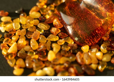 Amber. Many beautiful pieces of red-yellow polished amber with blurred background. Small and large pieces of amber on black background. Side view