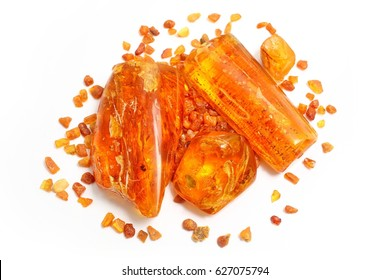 Amber. Many beautiful pieces of red-yellow polished amber on white  background. Small and large pieces of amber on a white background. Transparent amber with inclusions. Top view.