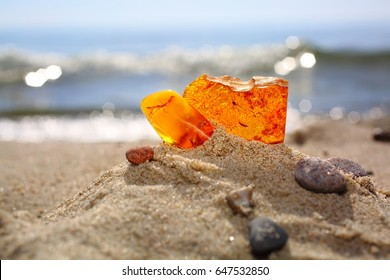 Amber on a sandy beach. Two pieces of a transparent mineral of a sunstone against a background of a sea. Ancient resin with  insects against the background of water and sand. Semiprecious stones.