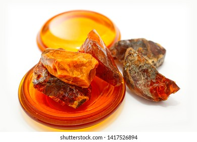 Amber. Pieces of ancient petrified resin. Natural mineral and crystal. Transparent amber circles. Sunstone in different forms. Natural material for jewelers. White background. Japan amber