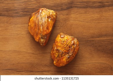 Amber raw unprocessed natural mineral stone amber, a collection of natural stones on a background of natural wood black walnut. A beautiful untreated stone. Flat lay.