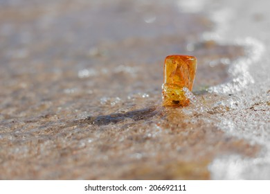 amber stone closeup at Baltic shore, water and sand natural background