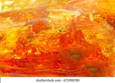 Amber texture background. An unusually beautiful amber background of different colors. Bright natural texture of amber. Sunstone as a texture  jewelers. Amber with inclusions under high magnification.
