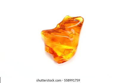 Amber. Transparent yellow amber. A unique piece of amber with a wavy surface on a white background. View from above