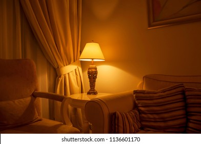 An ambient lighting in the living room. A classic decorative table lamp with shade at the side of the sofa.