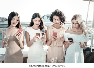 Ambiguous reaction. Good-looking cute girls messaging keeping goblets of champagne and looking at theirs gadgets.