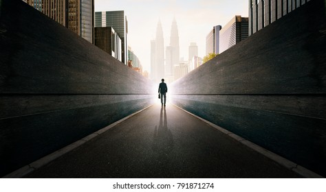Ambitions concept with businessman walking from alley to modern city .