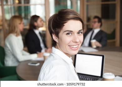 Ambitious attractive smiling young businesswoman looking at camera at group meeting, happy executive manager, team leader, successful professional interpreter or business coach head shot portrait
