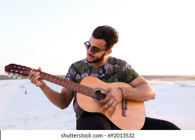 Ambitious budding musician, Muslim guy performs lyrical melody on musical instrument and guitar, and raises skill of professionalism, sitting on sandy hill in middle of wide sandy desert on warm