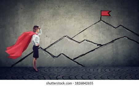 Ehrfeine Geschäftsfrau mit roter Flagge auf den Berggipfel schauend