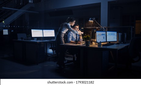 Ambitious, Confident Businessman Uses Desktop Computer, His Female Project Manager Explains Specific Tasks, Account Handling and Strategic Moves. Professional People Late at Night in Corporate Office