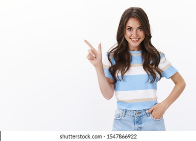 Ambitious gorgeous european woman with curly long hairstyle smiling inspired and thrilled, suggest go check out together awesome new cafe, pointing upper left corner smiling excited