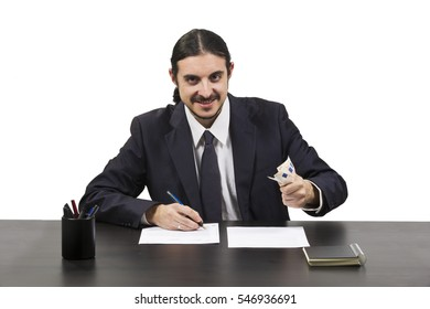 Ambitious greedy businessman grasping a handful of money as he sits working on paperwork at his desk looking at the camera in triumph