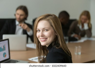 Ambitious smiling young businesswoman at group meeting, happy executive manager, team leader or professional looking at camera, successful woman representative or business coach head shot portrait