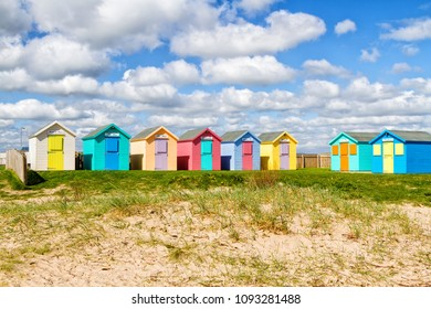 AMBLE, UNITED KINGDOM - APRIL 30, 2018: Traditional British beach huts on a bright sunny day. Vacation concept in Northumberland, United Kingdom