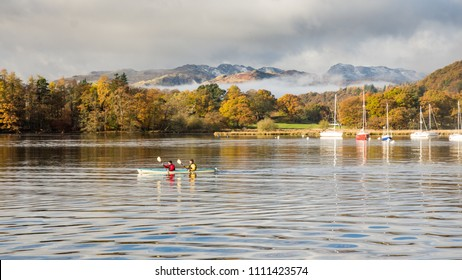 Ambleside, England, UK - November 12, 2016: Two people paddle a canoe in Windermere lake at Ambleside, under the mountains of Langdale and autumn woodland in England's Lake District National Park.