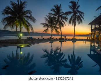 Ambon, Indonesia - February 10, 2018: View with silhouettes of  palm trees around luxury swimming pool during a tropical sunset. Ambon Island. Indonesia