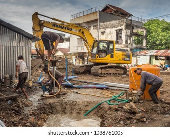 Ambon, Indonesia - February 17, 2018: Workers pumping the water at street of Ambon.