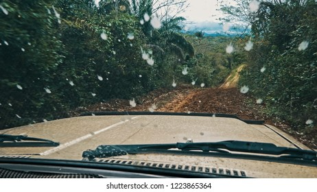 Amboro National Park / Bolivia - 10 OCT 2018 : a 4x4 car suv vehicle driving on a remote muddy dirt road across the rainforest