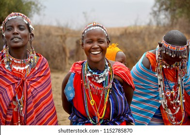 Amboseli National Park, Kenya, September, 2014. Beautiful maasai tribe women with traditional colorful ornaments (necklace, earrings) smiling and greeting tourists with traditional jumping dance