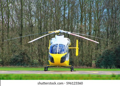 Ambulance helicopter. Yellow helicopter on the ground in front of forest, England UK.