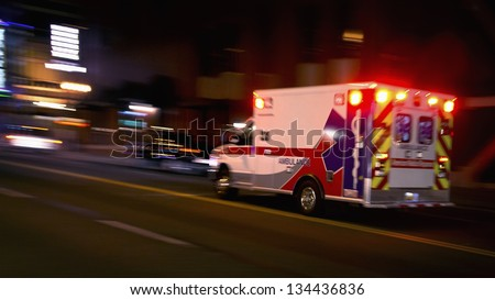 An ambulance speeding through traffic at nighttime