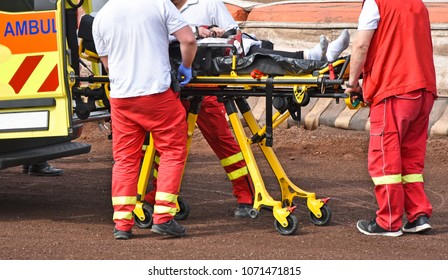 Ambulance stuff  with a stretcher on the sport track