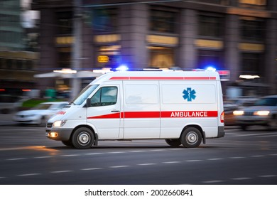Ambulance Van on a wide city street. White emergency vehicle with warning lights and siren moving fast an avenue. Metropolis rescue services transport. Motion blur and selected focus