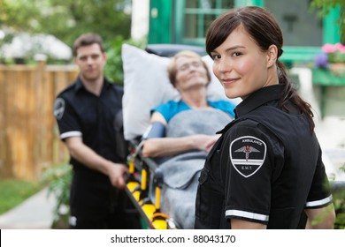 Ambulance worker portrait with stretcher, paitient and co-worker