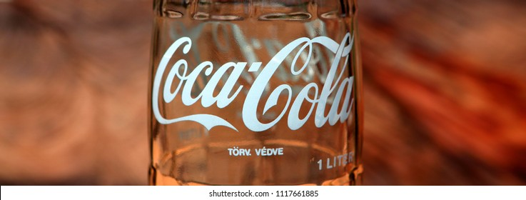 Ameland, Dutch - 21 June 2018.: White text Coca Cola and wooden background.  The carbonated soft drink is produced by The Coca-Cola Company.