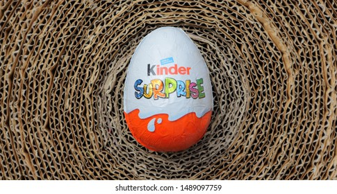 Ameland, Dutch - April 04, 2013: Kinder Surprise Egg on abstract background. Each Kinder Surprise egg consists of a chocolate shell, a plastic capsule with toy, and external foil wrap.