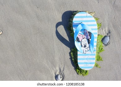 Ameland, Dutch - July 3, 2018.: Minnie Mouse on little children shoe, North sea beach, Holland. Pollutions and garbages on the beach