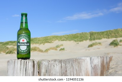 Ameland, Dutch - OCTOBER 3, 2018: Bottle of Heineken Lager Beer on North sea beach. Heineken is the flagship product of Heineken International