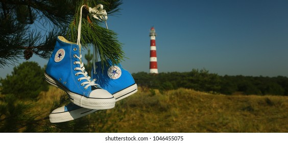 AMELAND, HOLLAND - 12 AUGUST 2015.: CONVERSE ALL STAR. Converse shoe and lighthouse on island Ameland. North sea.