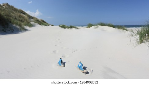 Ameland, Netherland - 2 October 2018.: Converse All Star Sneakers on the sand beach. North sea beach.