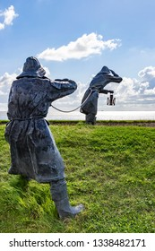 Ameland / Netherlands - 08-19-2017: Art on the dike of the island Ameland (statues of two people in rain gear peering over the water)