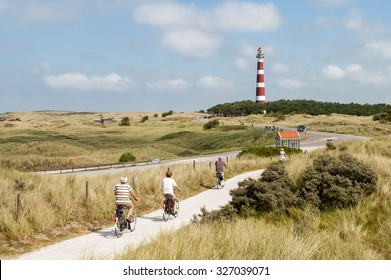 AMELAND, NETHERLANDS - AUG 14, 2004: Seniors riding on bicycles in the dunes of Ameland near the lighthouse, Netherlands