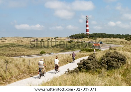 AMELAND, NETHERLANDS - AUG 14, 2004: Seniors riding on bicycles in the dunes of Ameland near the lighthouse, Netherlands